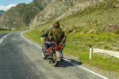 Dois indivíduos sem capacetes montam em uma motocicleta vermelha soviética velha sobre imagem de stock royalty free