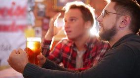 Dois indivíduos sentam-se na barra, bebendo a cerveja video estoque