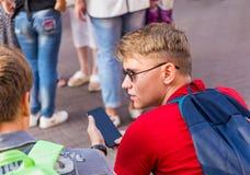 Dois indivíduos sentam-se sobre em um banco e olham-se algo no smartphone fotografia de stock royalty free