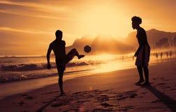 Dois indivíduos que jogam o futebol na praia no Rio no por do sol Foto de Stock