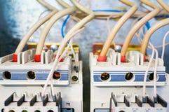 Dois interruptores trifásicos elétricos conectados por fios em um fundo do metal foto de stock