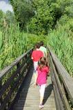 Dois irmãos com a irmã mais nova que anda abaixo da passarela Fotografia de Stock