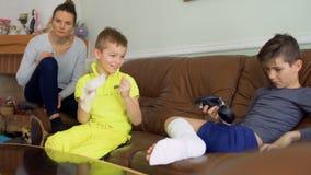 Dois irmãos com mão e pé quebrados estão enganando em casa o assento no sofá filme