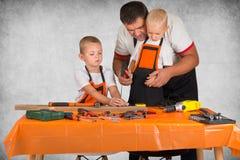 Dois irmãos com o paizinho que trabalha na oficina da carpintaria Pregos do martelo em um jogo de madeira com úmido imagem de stock