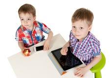 Dois irmãos com um PC da tabuleta Foto de Stock