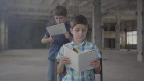 Dois irmãos de gêmeos pequenos na sala fumarento Um menino iluminou o papel com um isqueiro e uma outra leitura da criança no video estoque