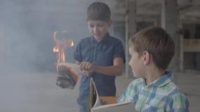Dois irmãos de gêmeos pequenos na sala fumarento Um menino iluminou o papel com um isqueiro e uma outra leitura da criança no vídeos de arquivo