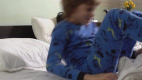 Dois irmãos encontram-se para baixo na cobertura branca coberta cama, então a criança levanta-se e começa-se dançar na cama filme