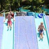 Dois irmãos felizes que têm o divertimento no parque do aqua fotos de stock royalty free