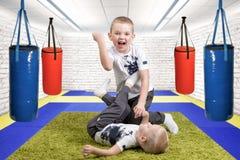 Dois irmãos jogam, para ter o divertimento, fazem amigos Meninos que atracam-se, esportes no gym Sucesso, emoções, apreciando a v fotografia de stock