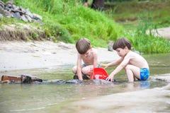 Dois irmãos louros estão tendo o divertimento na praia em um dia de verão ensolarado imagens de stock