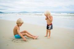 Dois irmãos louros que jogam na areia perto da água do mar em uma praia imagem de stock royalty free