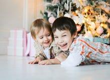 Dois irmãos mais novo que encontram-se no assoalho perto de uma árvore de Natal imagem de stock royalty free
