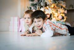 Dois irmãos mais novo que encontram-se no assoalho perto de uma árvore de Natal imagens de stock