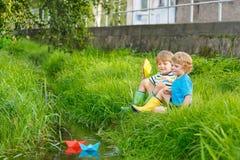 Dois irmãos mais novo que jogam com barcos de papel por um rio Fotos de Stock Royalty Free