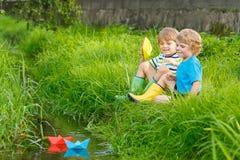 Dois irmãos mais novo que jogam com barcos de papel por um rio Foto de Stock