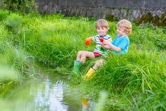 Dois irmãos mais novo que jogam com barcos de papel por um rio Fotografia de Stock