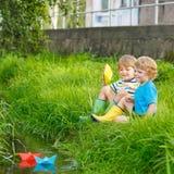 Dois irmãos mais novo que jogam com barcos de papel por um rio Foto de Stock Royalty Free