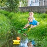 Dois irmãos mais novo que jogam com barcos de papel por um rio Imagens de Stock