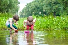 Dois irmãos mais novo que jogam com barcos de papel por um rio no dia de verão morno e ensolarado Imagens de Stock