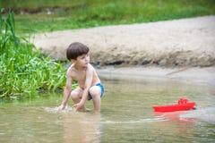 Dois irmãos mais novo que jogam com barcos de papel por um rio no dia de verão morno e ensolarado Foto de Stock