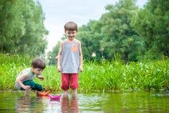 Dois irmãos mais novo que jogam com barcos de papel por um rio no dia de verão morno e ensolarado Fotografia de Stock Royalty Free