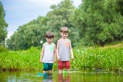 Dois irmãos mais novo que jogam com barcos de papel por um rio no dia de verão morno e ensolarado Fotos de Stock Royalty Free