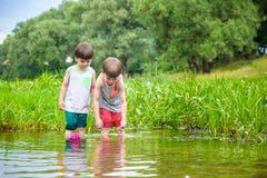 Dois irmãos mais novo que jogam com barcos de papel por um rio no dia de verão morno e ensolarado Fotos de Stock