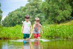 Dois irmãos mais novo que jogam com barcos de papel por um rio no dia de verão morno e ensolarado Foto de Stock Royalty Free