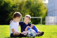 Dois irmãos mais novo que têm o divertimento que joga um jogo de futebol Foto de Stock Royalty Free