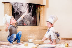 Dois irmãos - menino e menina - em chapéus do ` s do cozinheiro chefe perto da chaminé que senta-se no assoalho da cozinha sujado Imagens de Stock Royalty Free