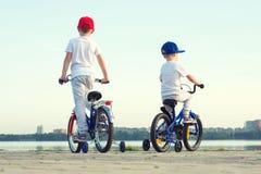 Dois irmãos montam uma bicicleta na margem fotografia de stock