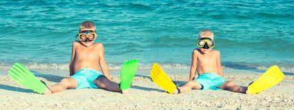 Dois irmãos nas máscaras e nas aletas estão sentando-se na praia Mergulhadores pequenos imagem de stock royalty free
