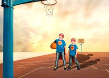 Dois irmãos no traje dos super-herói jogam o basquetebol imagem de stock royalty free