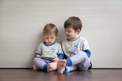 Dois irmãos nos mesmos pijamas jogam jogos no dispositivo foto de stock