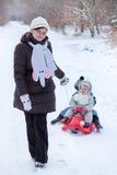 Dois irmãos pequenos e sua mãe que têm o divertimento no pequeno trenó Foto de Stock Royalty Free