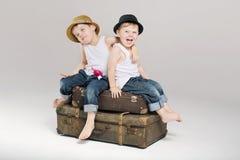 Dois irmãos pequenos que sentam-se nas malas de viagem Foto de Stock