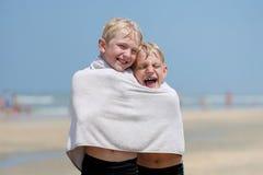 Dois irmãos que compartilham da toalha na praia fotografia de stock royalty free