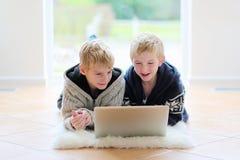 Dois irmãos que encontram-se no assoalho com portátil foto de stock