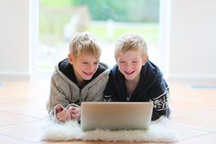 Dois irmãos que encontram-se no assoalho com portátil Imagens de Stock Royalty Free