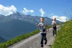 Dois irmãos que funcionam no trajeto da montanha fotos de stock royalty free