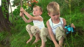 Dois irmãos que pescam no ar livre Dois pescadores pequenos na pesca Os irmãos mais novo sentam-se no banco de uma lagoa no filme