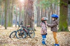 Dois irmãos que preparam-se para a equitação da bicicleta na mola ou no outono FO Imagem de Stock Royalty Free