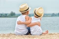 Dois irmãos que relaxam na praia do lago O rapaz pequeno abraça maciamente seu irmão mais idoso imagens de stock royalty free