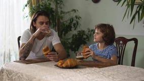 Dois irmãos que sentam-se na mesa de cozinha e que comem o croissant com cappuccino Relacionamento dos irmãos filme