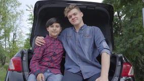 Dois irmãos que sentam-se na parte de trás do carro fora O homem que abraça o menino, pessoa que olha se do que no video estoque