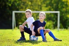Dois irmãos que têm o divertimento que joga um jogo de futebol Foto de Stock