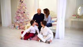 Dois irmãos são de sussurro e começando a partida olhar seus pais, sentando-se no assoalho no quarto com árvore de Natal video estoque