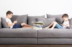 Dois irmãos sentam-se no lado oposto do sofá e olham-se em tablet pc fotos de stock royalty free