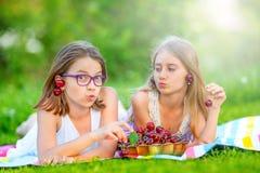Dois irmãs ou amigos bonitos em um jardim do piquenique encontram-se em uma plataforma e comem-se cerejas recentemente escolhidas Imagem de Stock